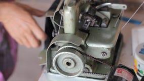 Mão de uma mulher que que usa a máquina de costura filme