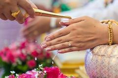 Mão de uma noiva que recebe a água santamente das pessoas idosas Imagem de Stock Royalty Free
