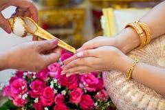 Mão de uma noiva que recebe a água santamente das pessoas idosas Fotos de Stock