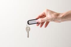 A mão de Womanque guarda uma chave Imagens de Stock Royalty Free