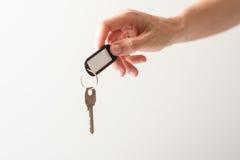 A mão de Womanque guarda uma chave Fotografia de Stock Royalty Free