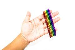 Mão de Womand que guarda um bracelete colorido do ímã das esferas Imagens de Stock