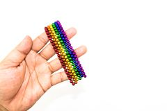 Mão de Womand que guarda um bracelete colorido do ímã das esferas Imagem de Stock