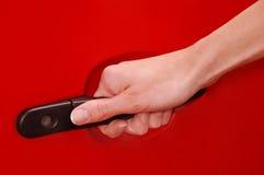 Mão de Womans no punho do carro Imagens de Stock