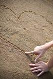 Mão de Womans que desenha um coração Foto de Stock