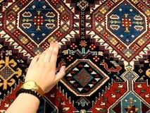 Mão delicada da mulher e dos tapetes orientais Testes padrões originais fotografia de stock