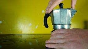 A mão desaparafusa um fabricante de café do mocha para introduzir o pó do café para preparar um café da manhã italiano típico video estoque