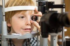 A mão do ótico que verifica o olho do menino com a lente imagens de stock