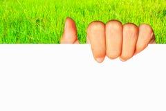 Mão do adolescente que mantém o negócio vazio do papel de placa branca prese Imagens de Stock