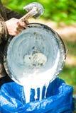 Mão do agricultor que guarda o depósito de leite da árvore da borracha Fotografia de Stock Royalty Free