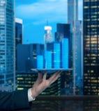 A mão do analista está guardando um dispositivo com projeção da carta de barra do rendimento previsto da empresa imagens de stock