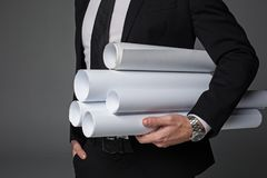 Mão do arquiteto que guarda rolos de papel diferentes imagens de stock royalty free