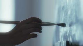 A mão do artista com uma escova tira na lona video estoque