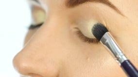 Mão do artista de composição do close-up, aplicando a sombra ao olho do ` s da mulher usando a escova 4K filme