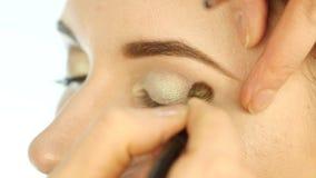 Mão do artista de composição do close-up, aplicando a sombra ao olho do ` s da mulher usando a escova Movimento lento video estoque