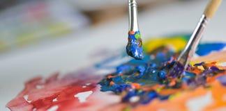 A mão do artista que aplica o guache da pintura na folha do desenho Imagens de Stock Royalty Free