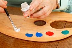 Mão do artista que coloca a pintura sobre a paleta Imagem de Stock Royalty Free