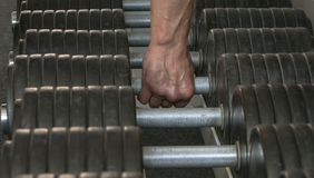 A mão do atleta toma o barbell do suporte no salão de esportes imagens de stock royalty free