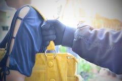 A mão do bandido rouba o saco uma outra pessoa no público sob Imagem de Stock Royalty Free
