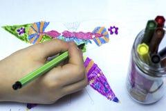 A mão do bebê com um marcador pinta uma borboleta no Livro Branco imagens de stock royalty free
