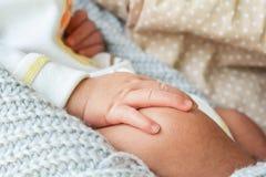 Mão do bebê no joelho na cama imagens de stock
