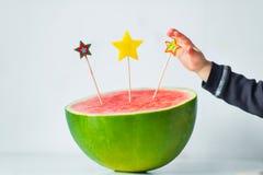 Mão do bebê que põe a vela no bolo de aniversário da melancia Fotos de Stock
