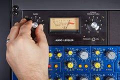 Mão do botão de giro do técnico audio no console imagens de stock royalty free