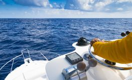 Mão do capitão no volante do barco de motor no oceano azul durante o dia da pesca Conceito da pesca do sucesso Iate do oceano fotografia de stock