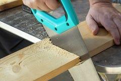 Mão do carpinteiro com o handsaw que corta placas de madeira fotos de stock