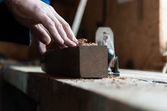 Mão do carpinteiro que limpa a placa de madeira de planeamento fotografia de stock royalty free