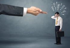 Mão do chefe que ateia fogo ao homem de negócios culpado Imagens de Stock