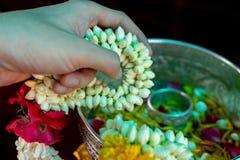 Mão do close up da pessoa que guarda a festão da flor com a folha e a pétala que flutuam na água no fundo foto de stock royalty free