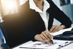 Mão do close-up das mulheres de negócio com escrita de papel no gráfico fotografia de stock royalty free