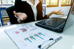 Mão do close-up das mulheres de negócio com escrita de papel no gráfico foto de stock