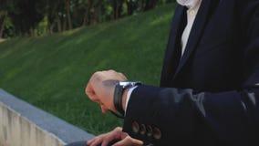 Mão do close-up de um homem com um pulso de disparo em um terno de negócio preto o homem de negócios olha o pulso de disparo em s filme