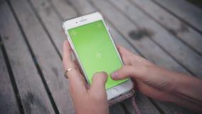 Mão do close up de uma jovem mulher que guarda e que usa o telefone verticalmente em uma tabela de madeira com chave verde da tel video estoque