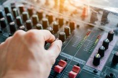 Mão do close-up que ajusta o som do misturador no painel audio fotografia de stock royalty free