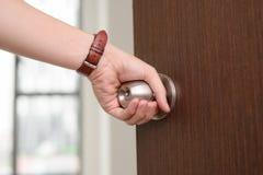 Mão do close-up que guarda o botão de porta, porta de abertura levemente, selectiv foto de stock