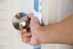 Mão do close-up que guarda o botão de porta, porta de abertura levemente, foco seletivo fotografia de stock royalty free
