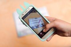 Mão do close-up usando o telefone que toma a foto na bebida do café fotos de stock