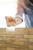 Mão do coordenador que joga um jogo da torre dos blocos & um x28 de madeira; jenga& x29; em azul Imagem de Stock Royalty Free