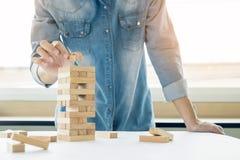 Mão do coordenador que joga um jogo da torre dos blocos & um x28 de madeira; jenga& x29; em azul Imagens de Stock