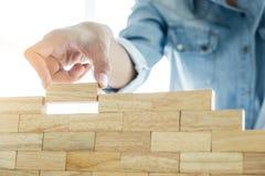 Mão do coordenador que joga um jogo da torre dos blocos & um x28 de madeira; jenga& x29; em azul Foto de Stock