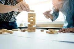 Mão do coordenador que joga um jogo da torre dos blocos & um x28 de madeira; jenga& x29; em azul Fotos de Stock