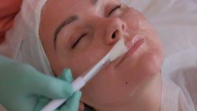 A mão do cosmetologist aplica o gel à cara fêmea com uma escova branca Menina bonita no sal?o de beleza Close-up pele video estoque