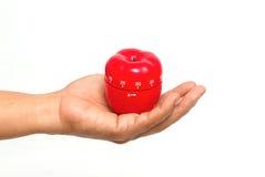 A mão do cozinheiro chefe com um temporizador da maçã Imagem de Stock Royalty Free
