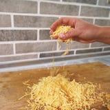 A mão do cozinheiro chefe derrama o queijo esmagado em uma placa de madeira imagens de stock