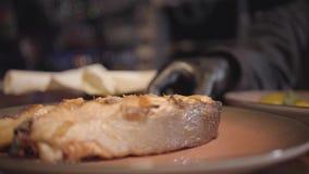 Mão do cozinheiro chefe do restaurante que põe a placa com parte grande de peixes grelhados dos salmões sobre a tabela video estoque
