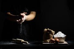 A mão do cozinheiro chefe trilha a farinha com o pino e os ingredientes de madeira do rolo Fotos de Stock Royalty Free