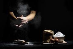 A mão do cozinheiro chefe trilha a farinha com o pino e os ingredientes de madeira do rolo Fotografia de Stock Royalty Free